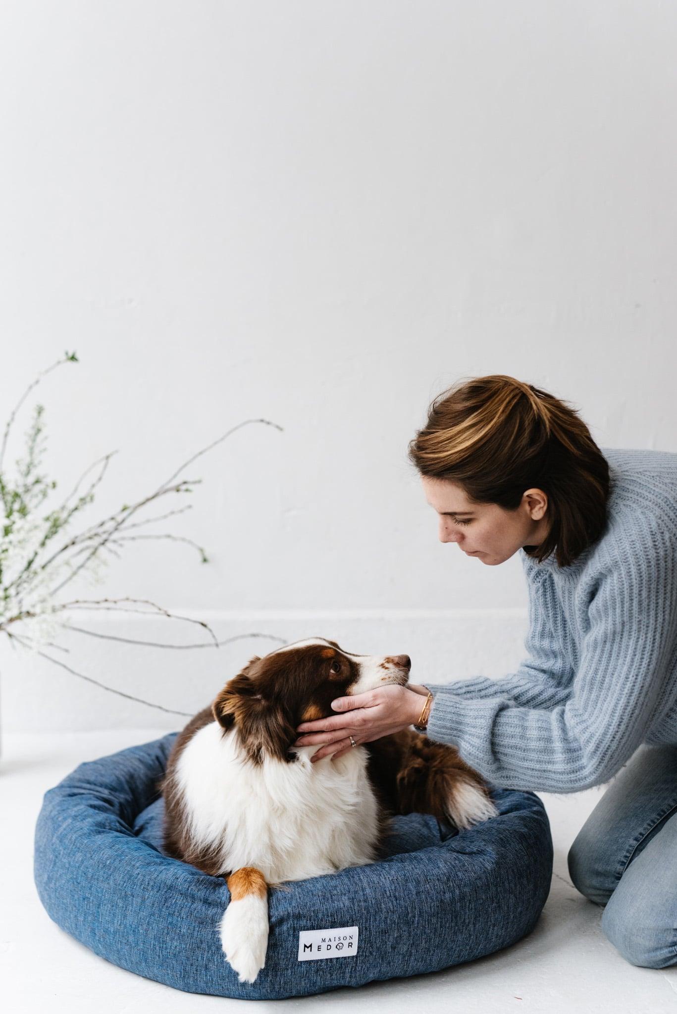 la fondatrice de la marque de coussins et paniers pour chien Maison Medor avec son chien dans un panier cesar