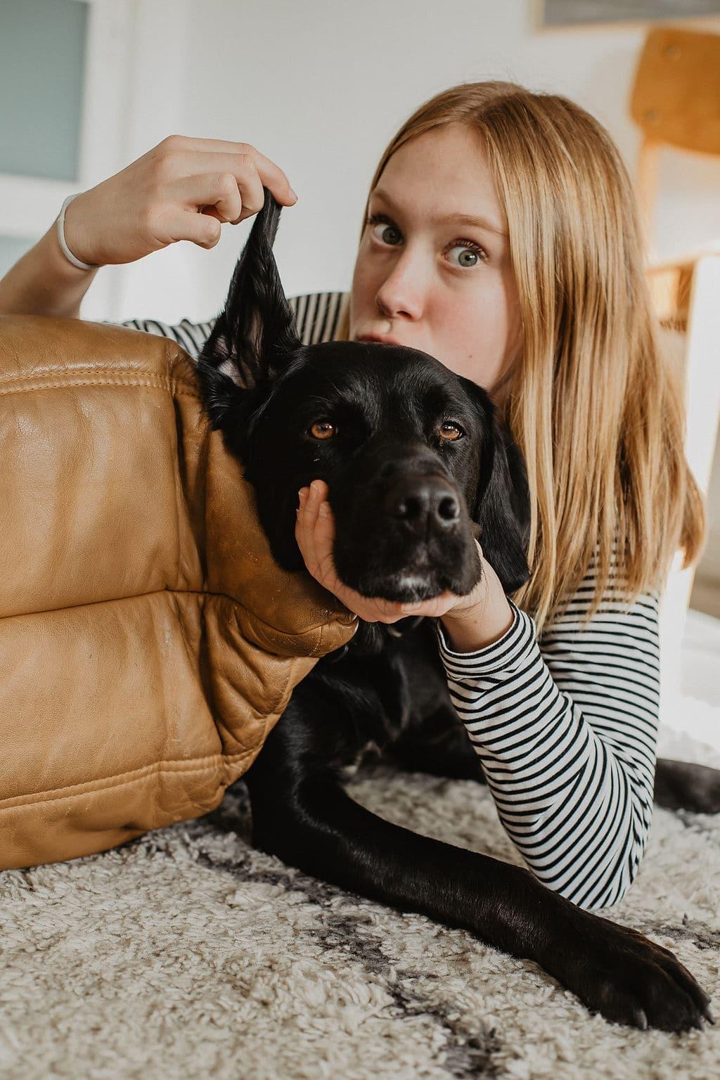 Le chien labrador fait un bisous a une jeune fille de la famille pour maison medor
