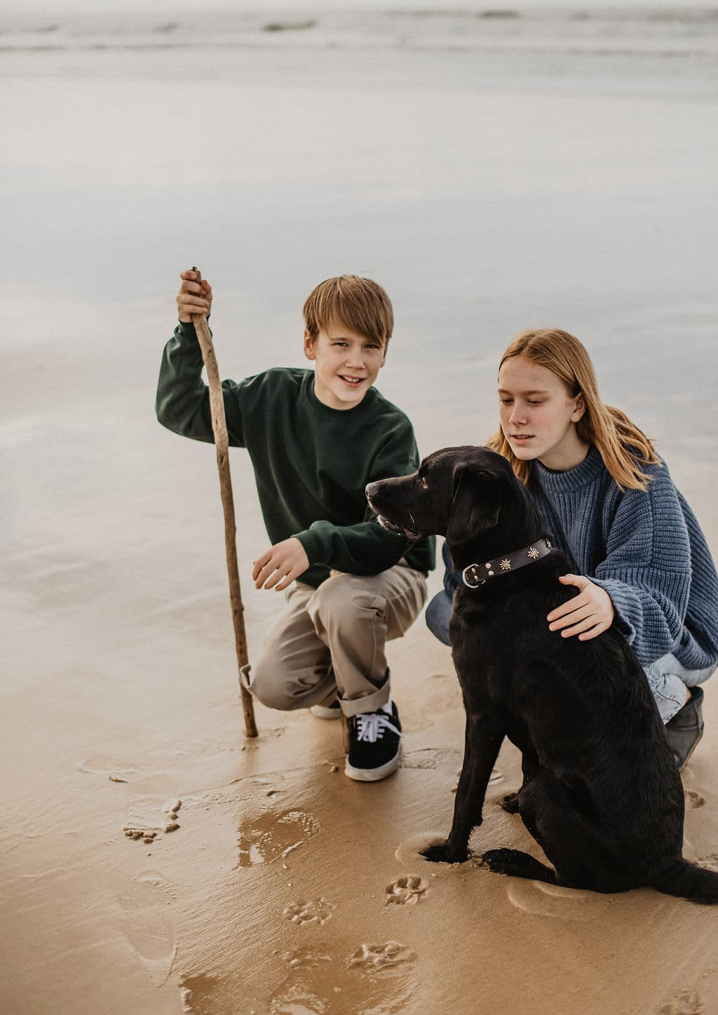 deux enfants sur la plage avec leur chien labrador pour Maison Medor